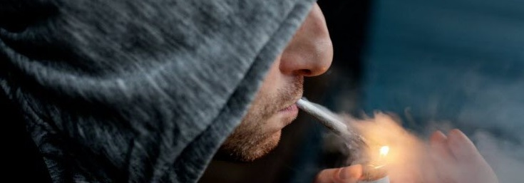 Un fumeur qui allume son joint